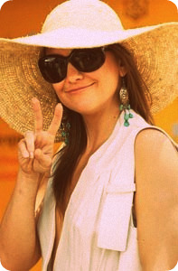 Kate Hudson giving the peace sign in boho jewelry and a floppy hat