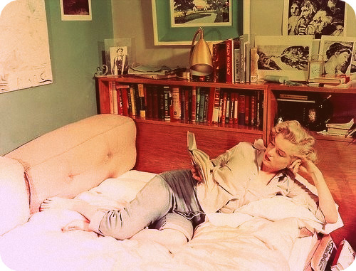 Marilyn Monroe in jeans reading on a couch